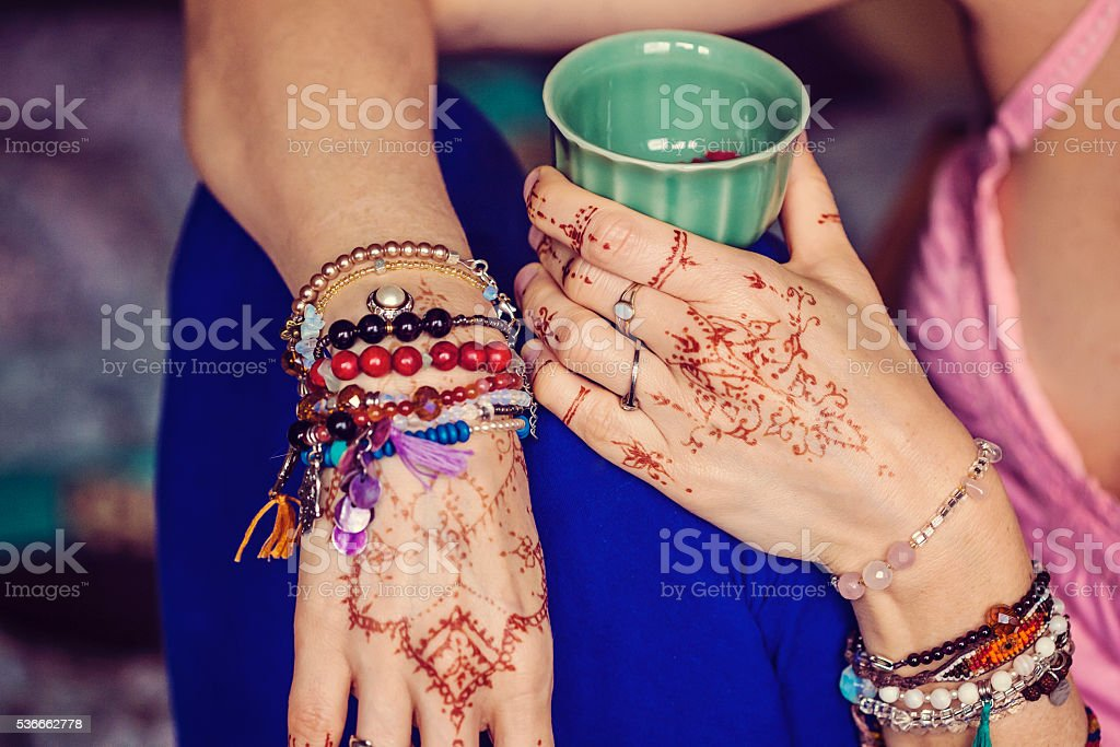 Female hands with mehndi and lot of bracelets stock photo
