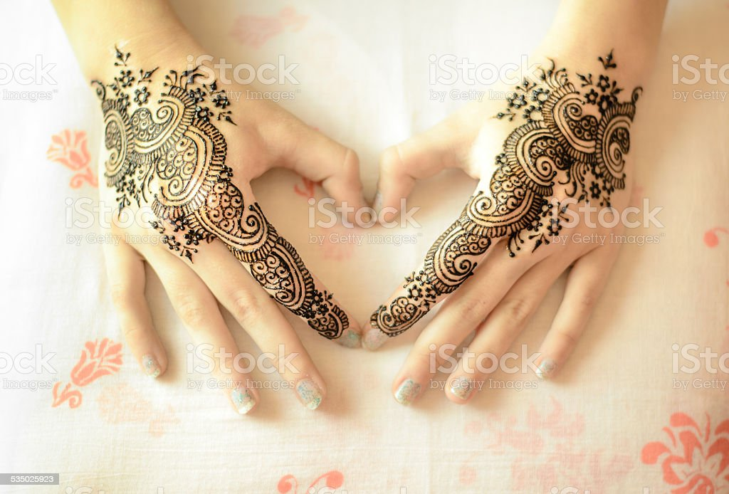 Female hands with mehndi decoration in heart shape stock photo
