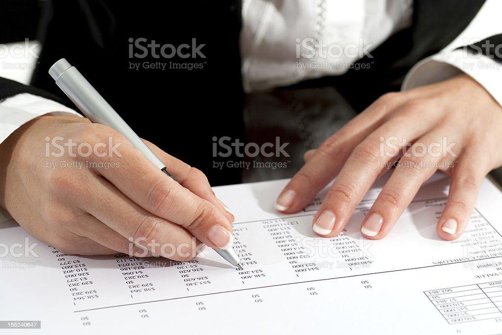 Mains de femme avec stylo examinant un document photo libre de droits
