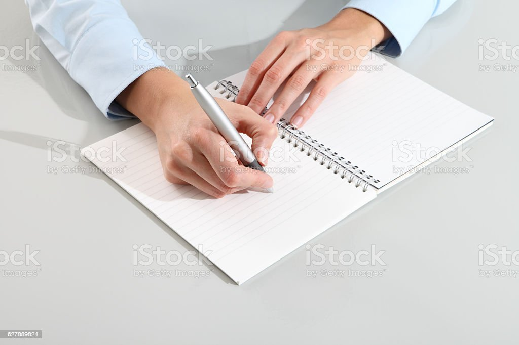 female hands with pen writing on notebook stock photo