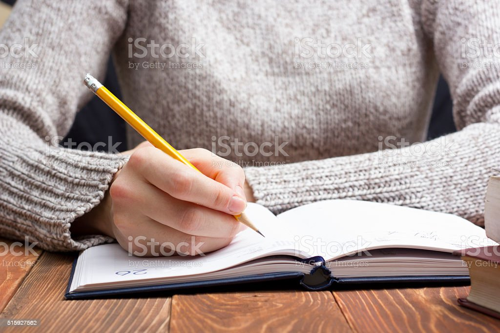 female hands with pencil writing on notebook stock photo