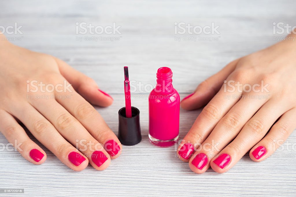 Female hands with red manicure and an open bottle stock photo