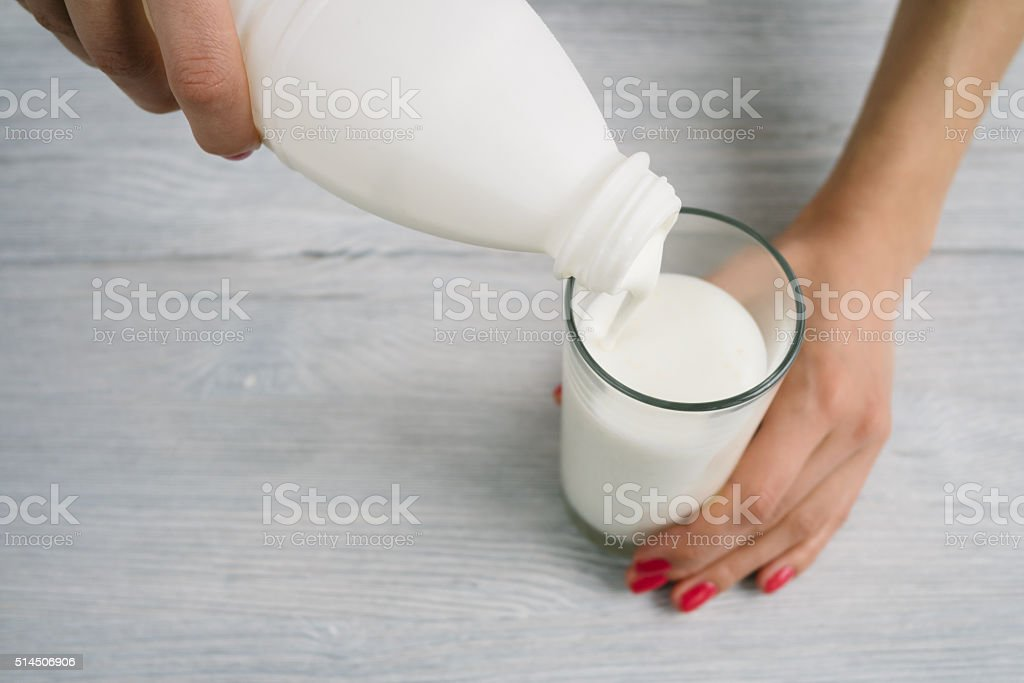 Female hands with red manicure poured the yogurt stock photo