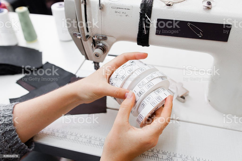 Female hands with rolls of size tag for clothes stock photo