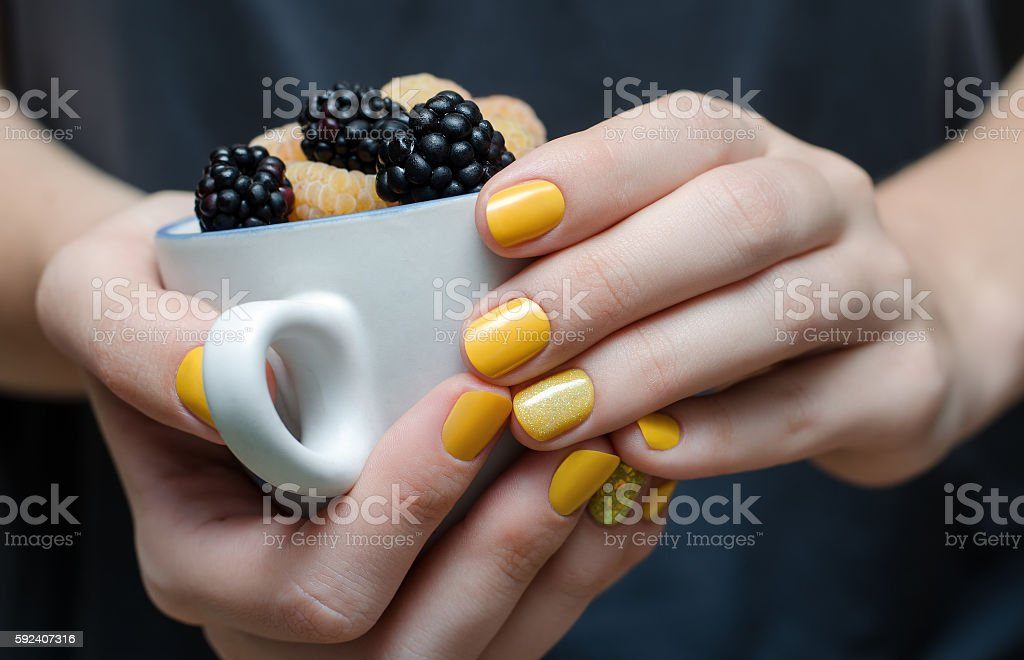 Female hands with yellow nail design. stock photo