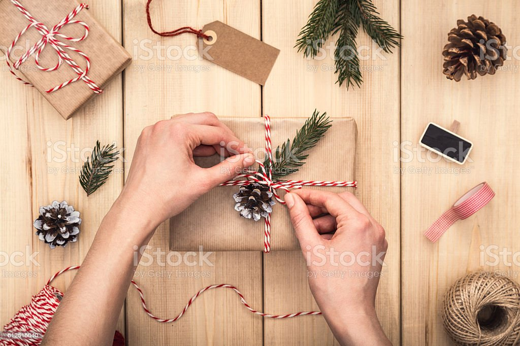 Female hands wrapping a gift over wooden table. Directly above. stock photo