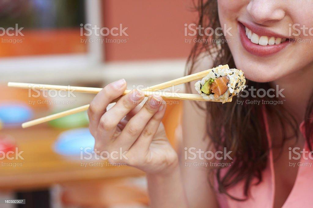 Female happily eating sushi with chopsticks  stock photo