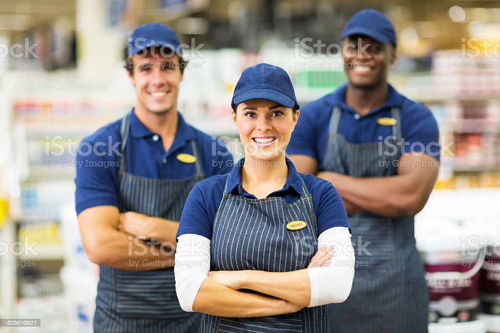 female hardware store worker and team stock photo