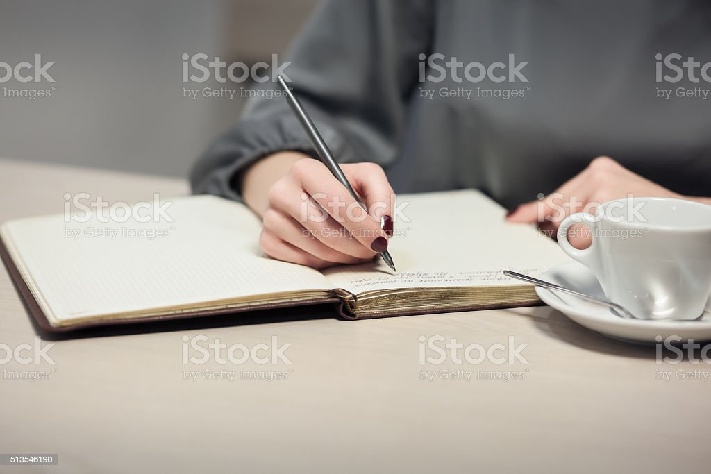 female has coffee break and writing notes in diary; stock photo