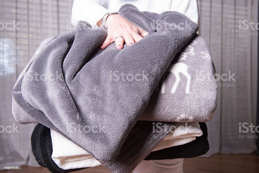 female helper welcomes refugees with warm blankets for cold nights stock photo