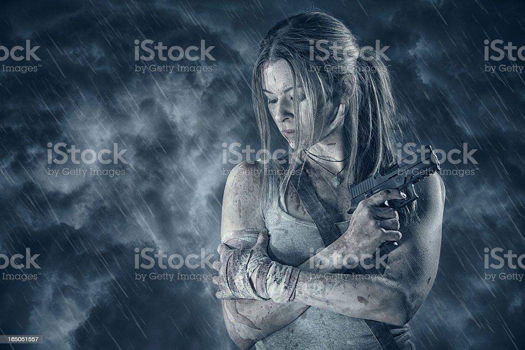 Female heroine holding pistol in rain stock photo