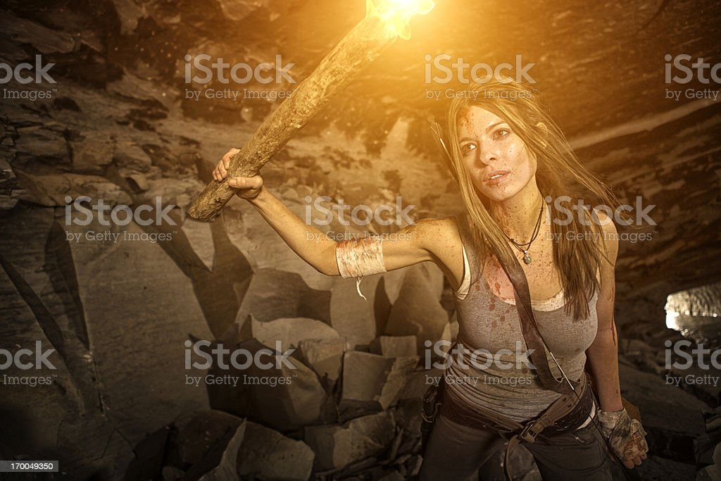 Female heroine looking in a cave with torch stock photo