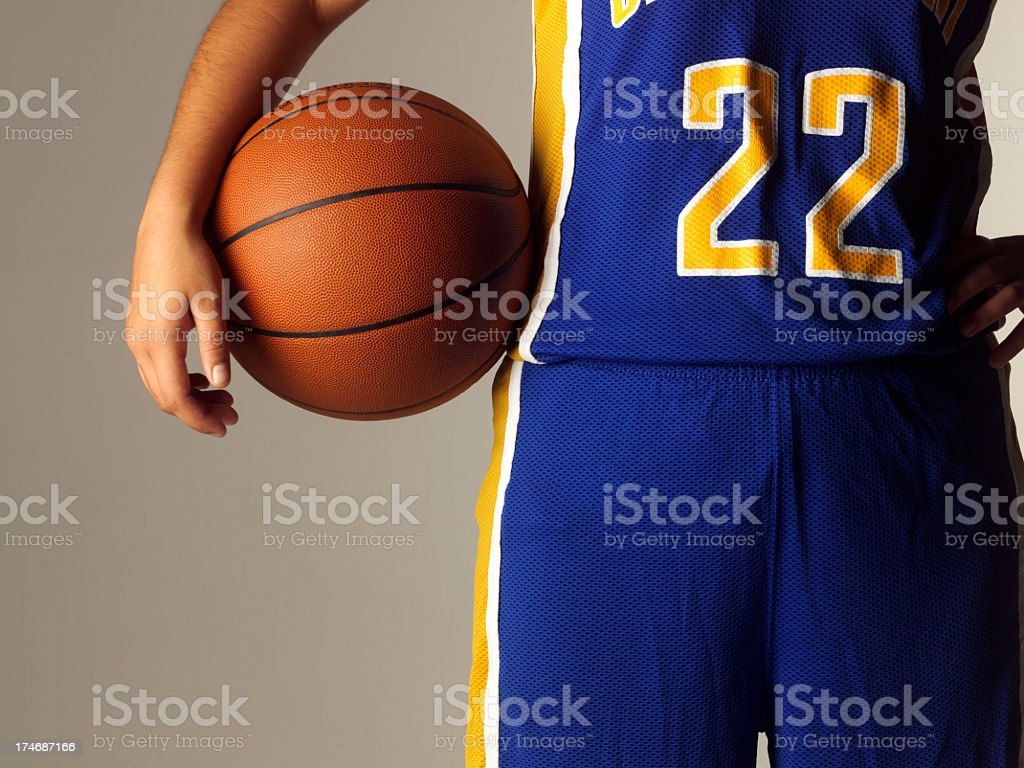 Female high school or college basketball player holding basketball stock photo
