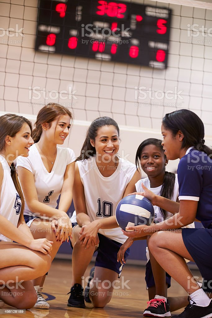 Female High School Volleyball Team Have Team Talk From Coach stock photo