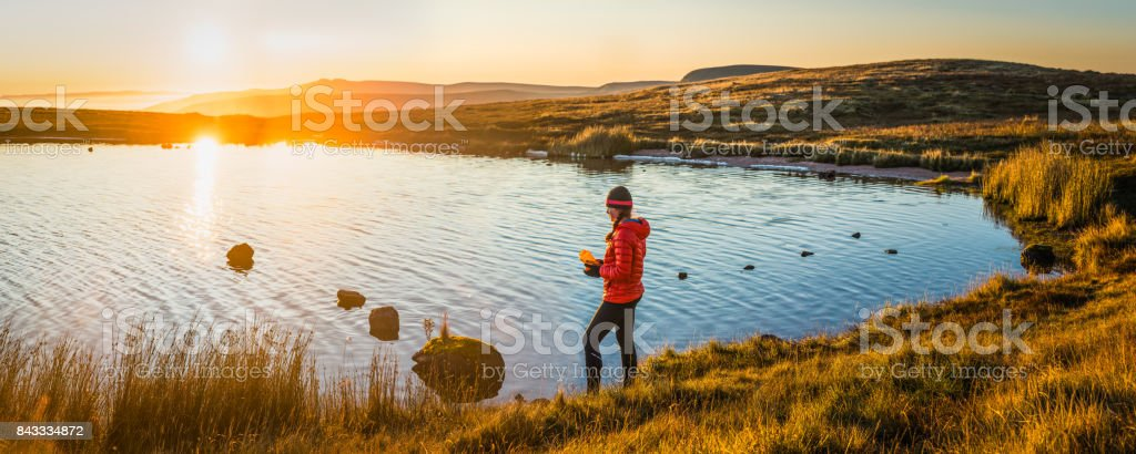 Teenage girl hiker in down jacket and woollen hat filling a water...
