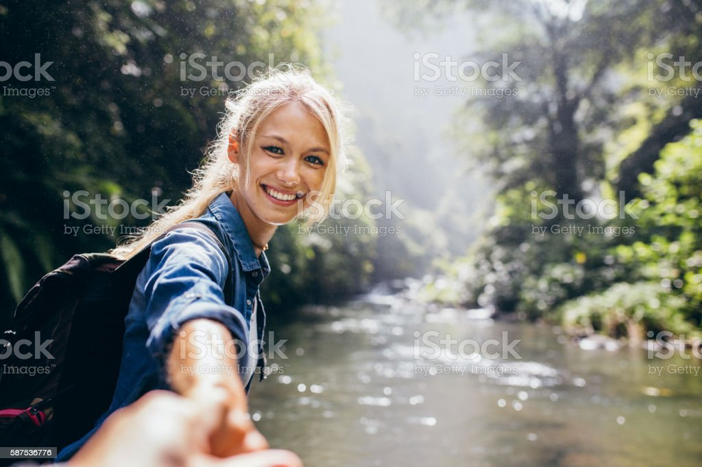 Female hiker holding hand of his boyfriend stock photo