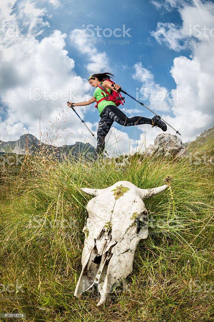 Female hiker jumping behind animal skull stock photo