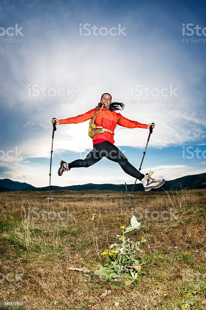 Female hiker jumping outdoors stock photo