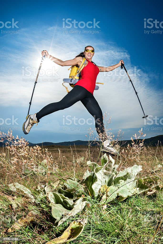 Female hiker jumping with poles stock photo