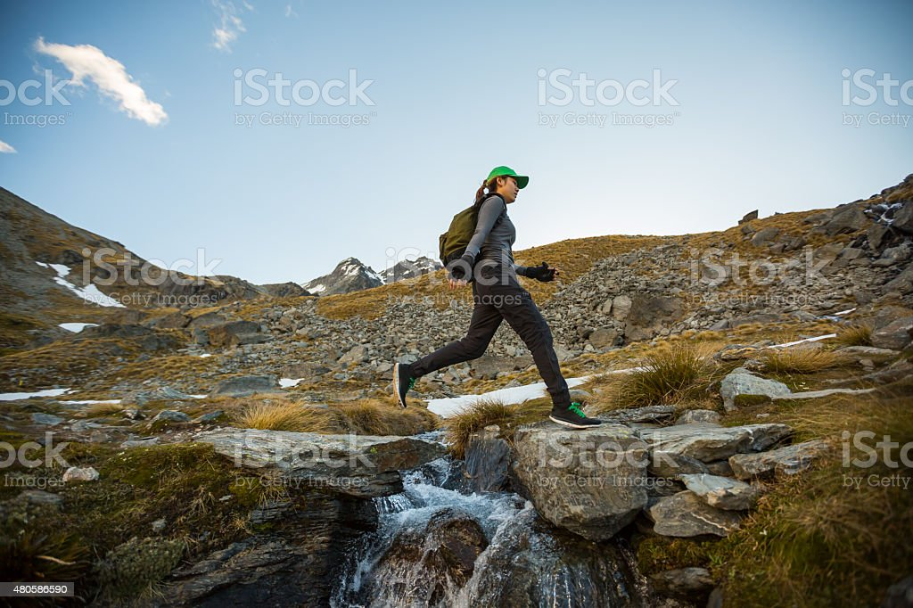 Female hiker leaping across a stream stock photo
