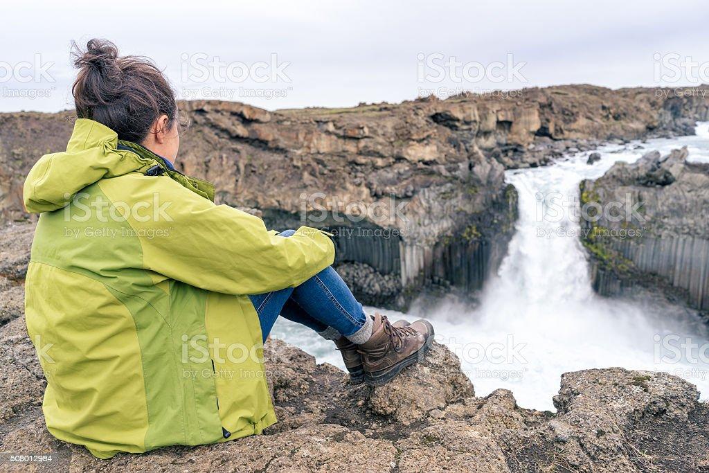 Female hiker looking at Aldeyjarfoss waterfall, Iceland. stock photo
