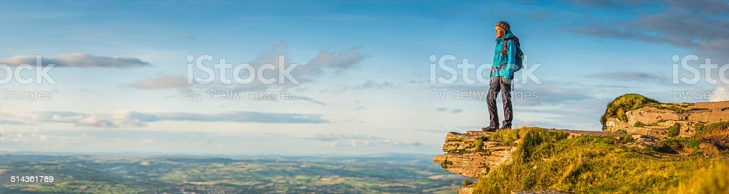 female hiker looking out over idyllic landscape from mountain top stock photo