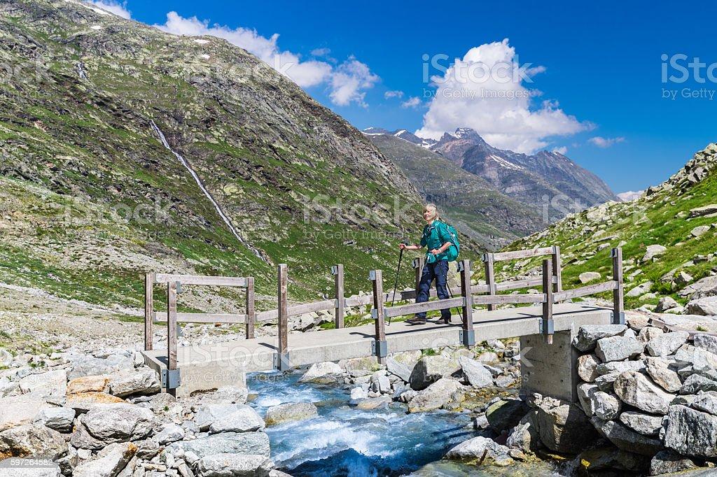 Female hiker on bridge over stream in mountains stock photo