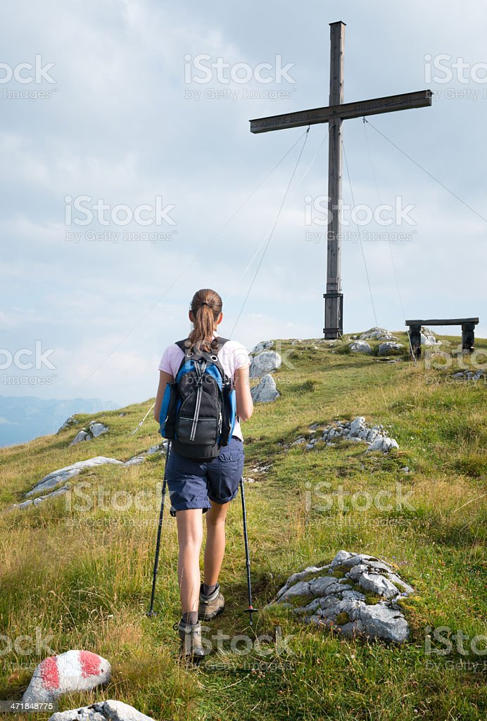 Female Hiker reaching the Mountain Summit Cross royalty-free stock photo