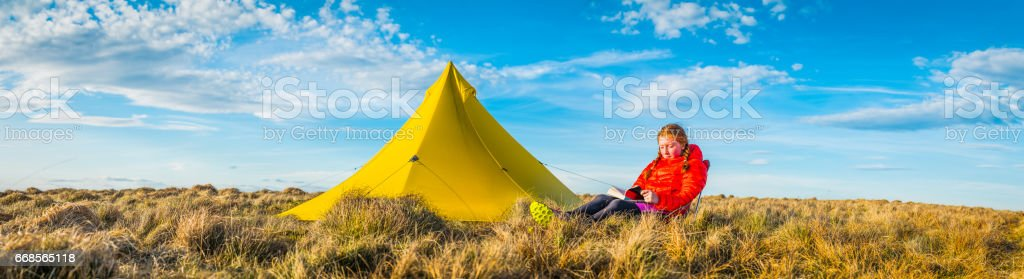 Female hiker reading book outside yellow tent on mountain panorama stock photo