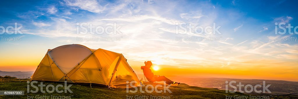 Female hiker relaxing outside tent on mountain at sunset panorama stock photo
