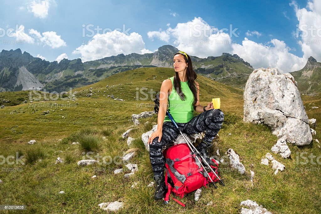 Female hiker resting in the mountains stock photo