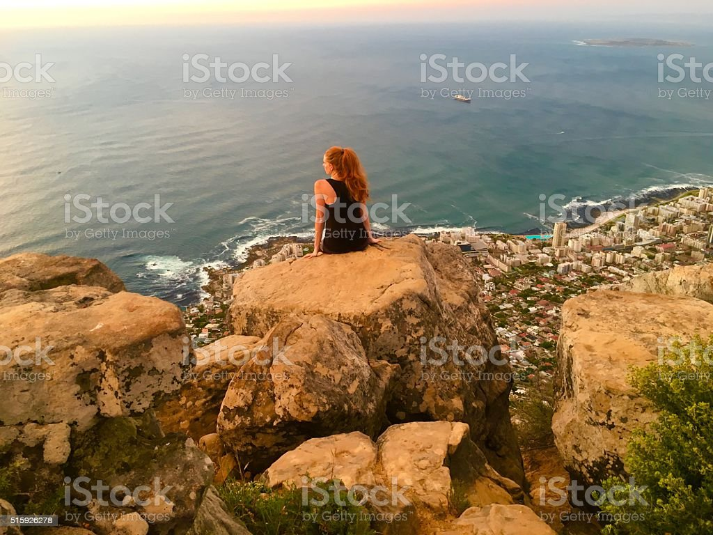 female hiker sitting on the edge of a cliff stock photo