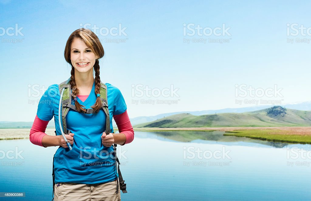 Female hiker standing at riverbank stock photo