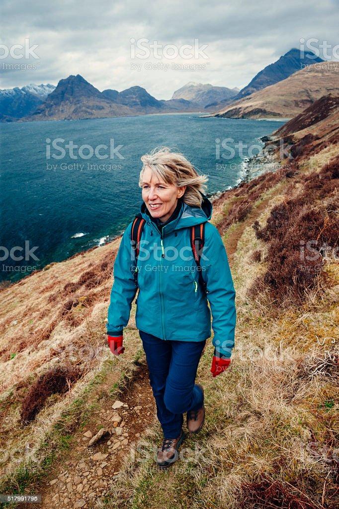Female hiker walking along coastal trail in Skye stock photo