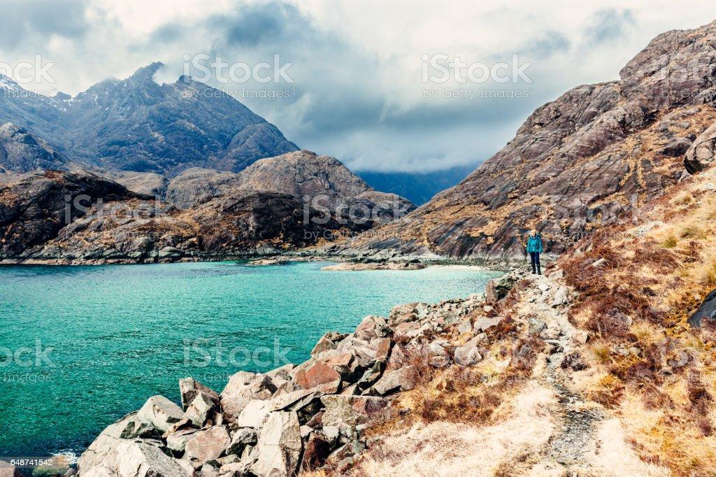 Female hiker walking coastal trail, Skye, Scotland stock photo