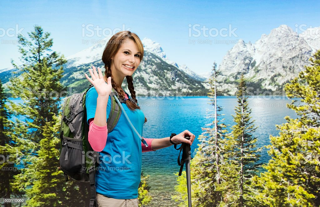 Female hiker waving hand in the wilderness area stock photo