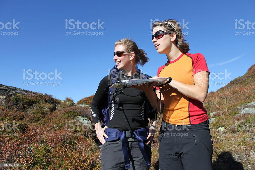 Female hikers reading map royalty-free stock photo
