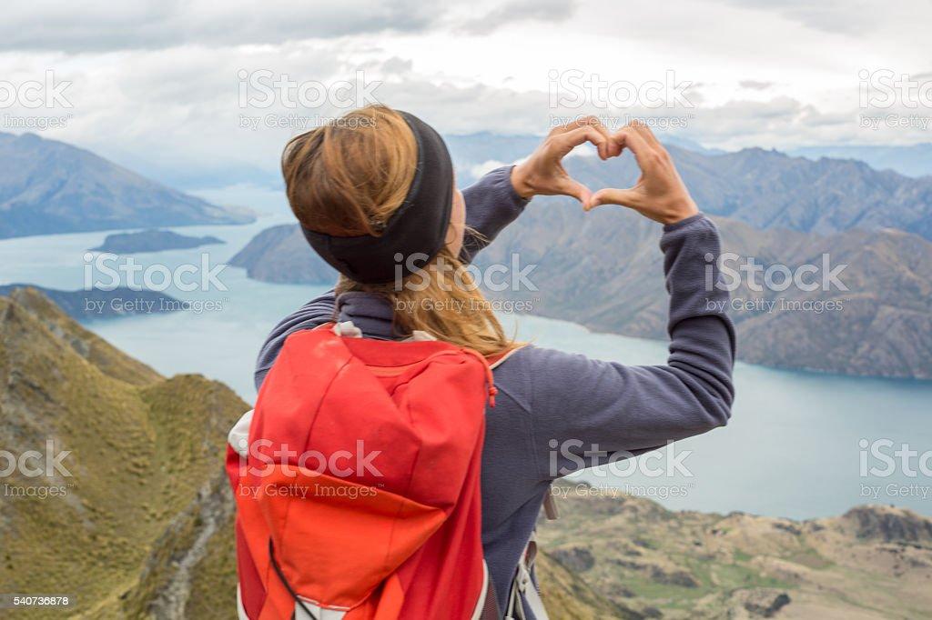 Female hiking makes heart shape finger frame towards nature stock photo