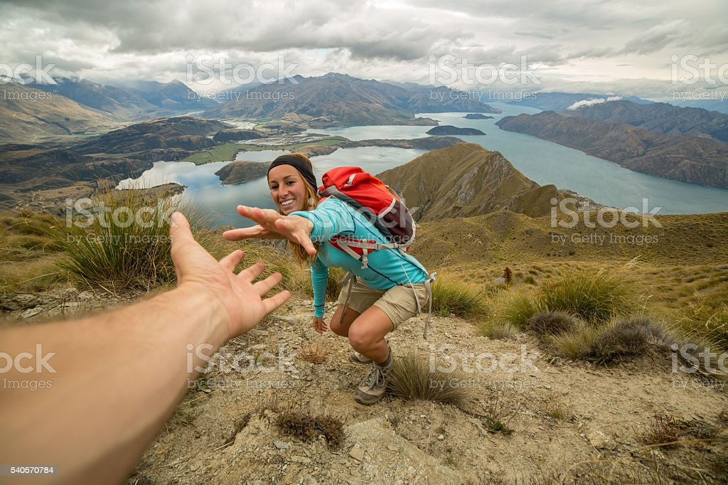 Female hiking pulls out hand to get assistance from teammate stock photo