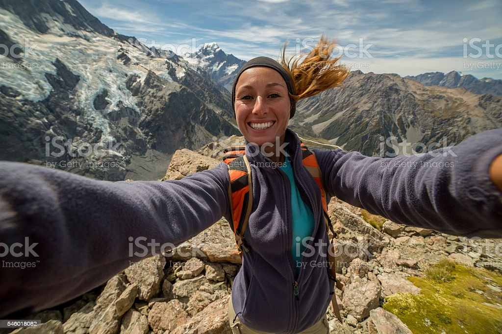 Female hiking reaches mountain top and takes selfie portrait stock photo