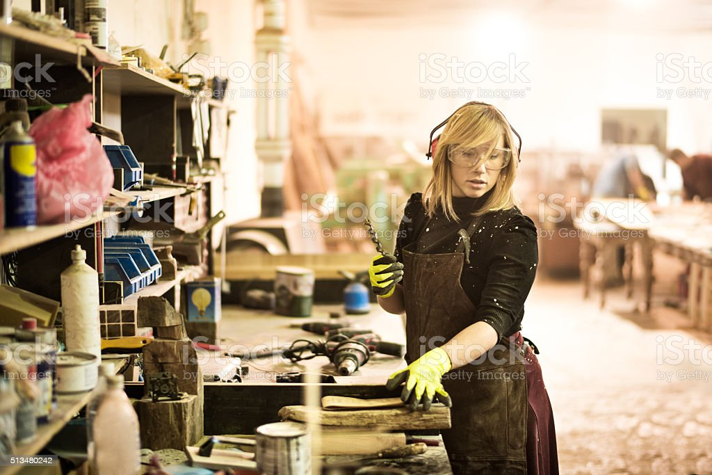 Female holding a drill bit in workshop stock photo