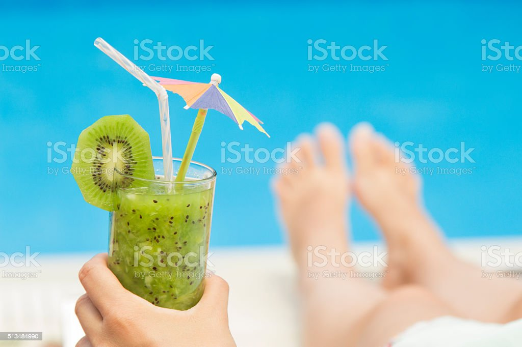 Female holding a glass of fresh kiwi smoothie stock photo