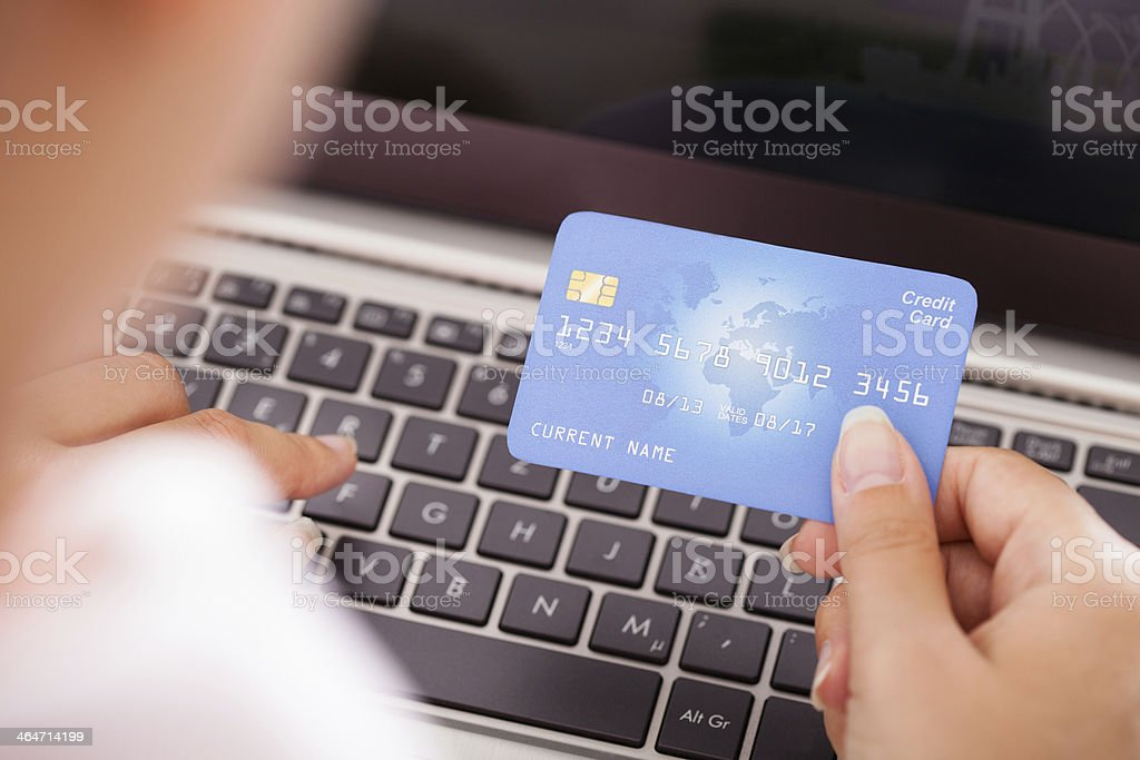 Female Holding Credit Card Over Keyboard stock photo