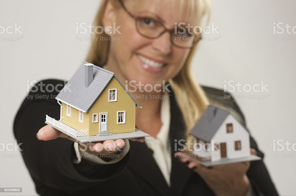 Female Holding Two Small Houses royalty-free stock photo
