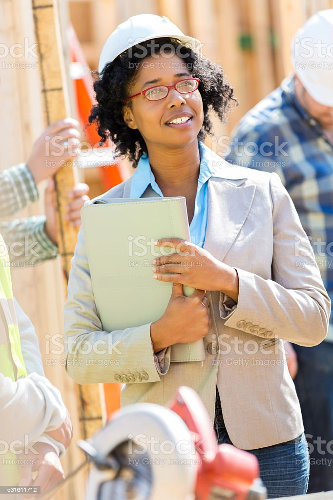 Female home builder visits work site stock photo