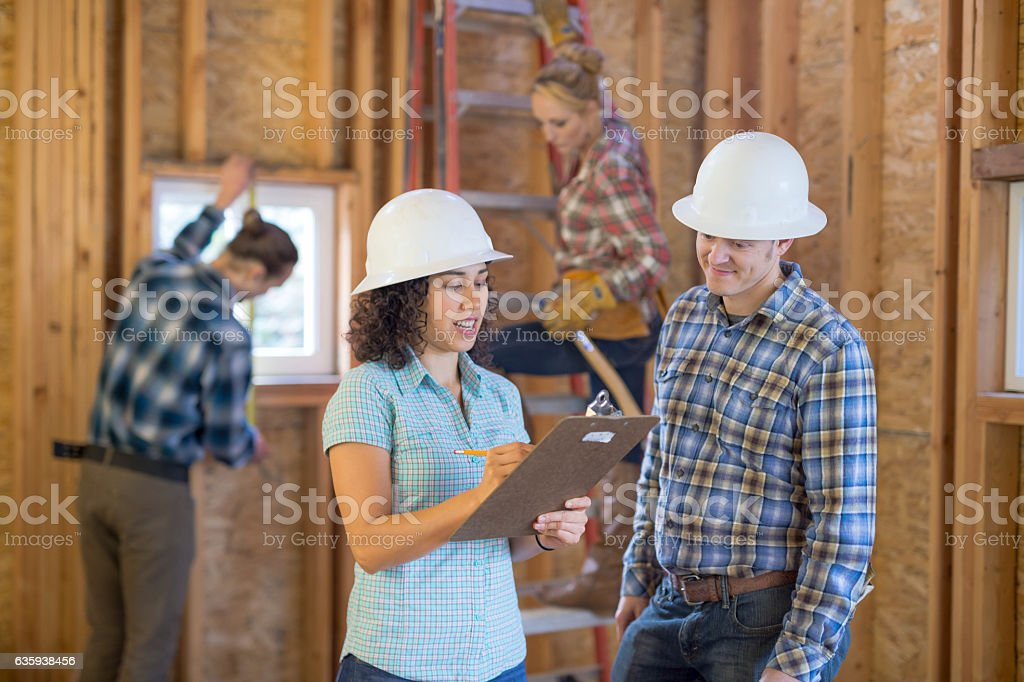 Female homeowner going over building plans with construction worker stock photo