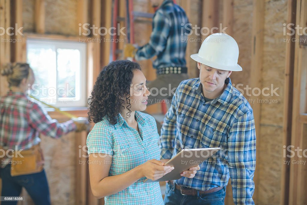 Female homeowner going over building plans with the general contractor stock photo