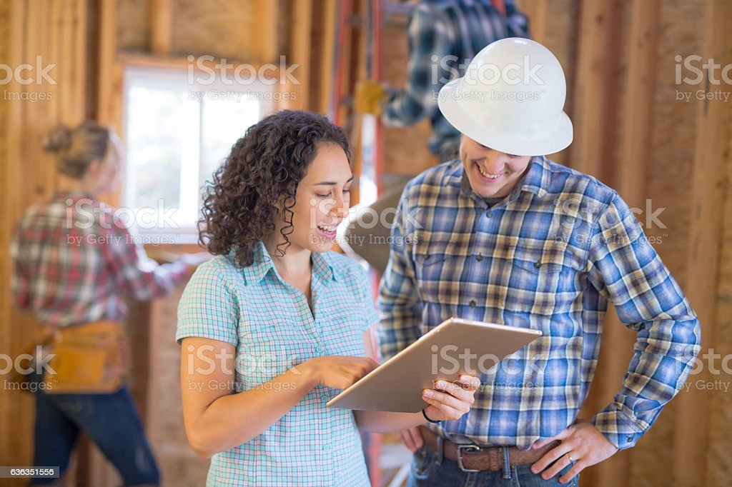 Female homeowner going over house building plans on stock photo