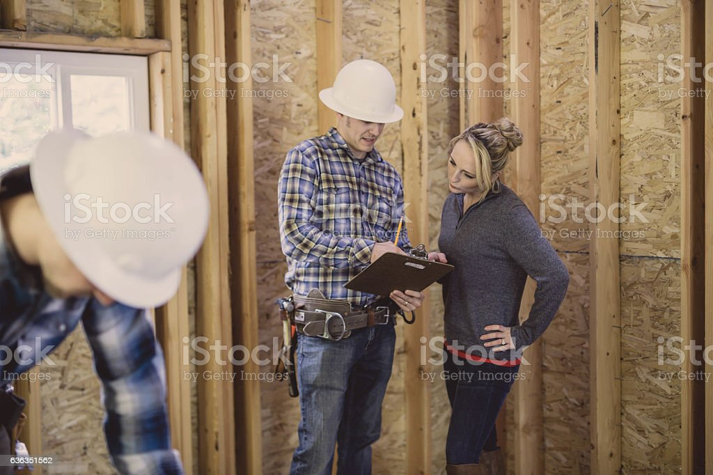 Female homeowner going over house building plans with contractor stock photo
