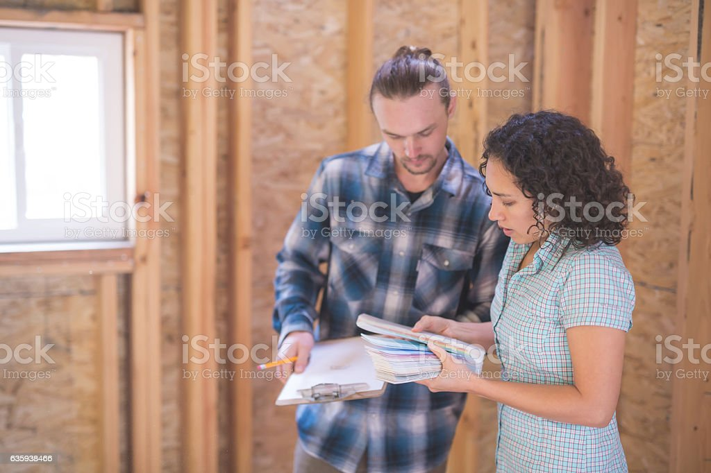 Female homeowner looking at paint chips with a male stock photo
